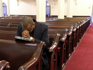 youngblackmanprayinginchurch
