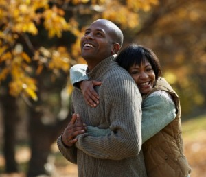 Black couple hugging in park in autumn