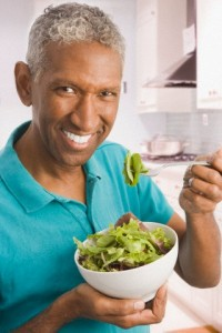 Mixed race man eating salad in kitchen