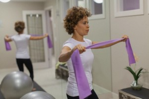 Woman using resistance band for workout.