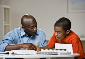 African American father helping son with homework