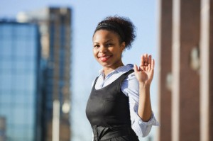 Portrait of smiling African American young woman in formals waving hand