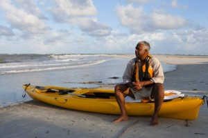 Black man sitting on beach with kayak